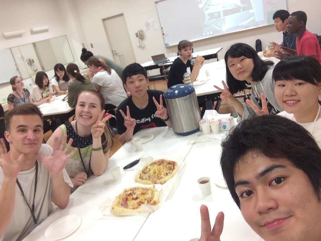 Eating pizza together with students of the Kumamoto Prefectural University